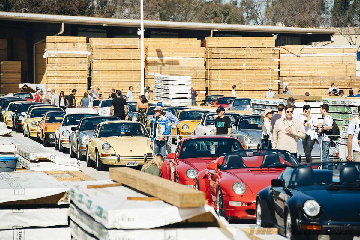 multiple red, yellow, grey, white, black, and orange air-cooled porsches in a lumberyard