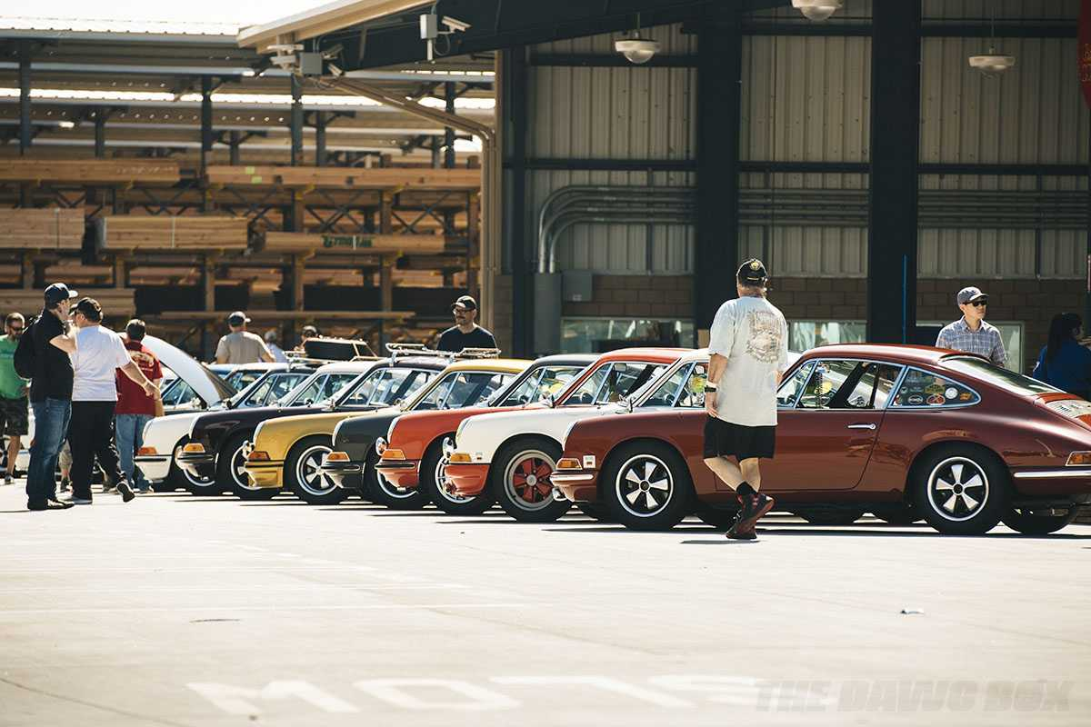 maroon red white yellow and black classic porsches lined up for display at a lumberyard