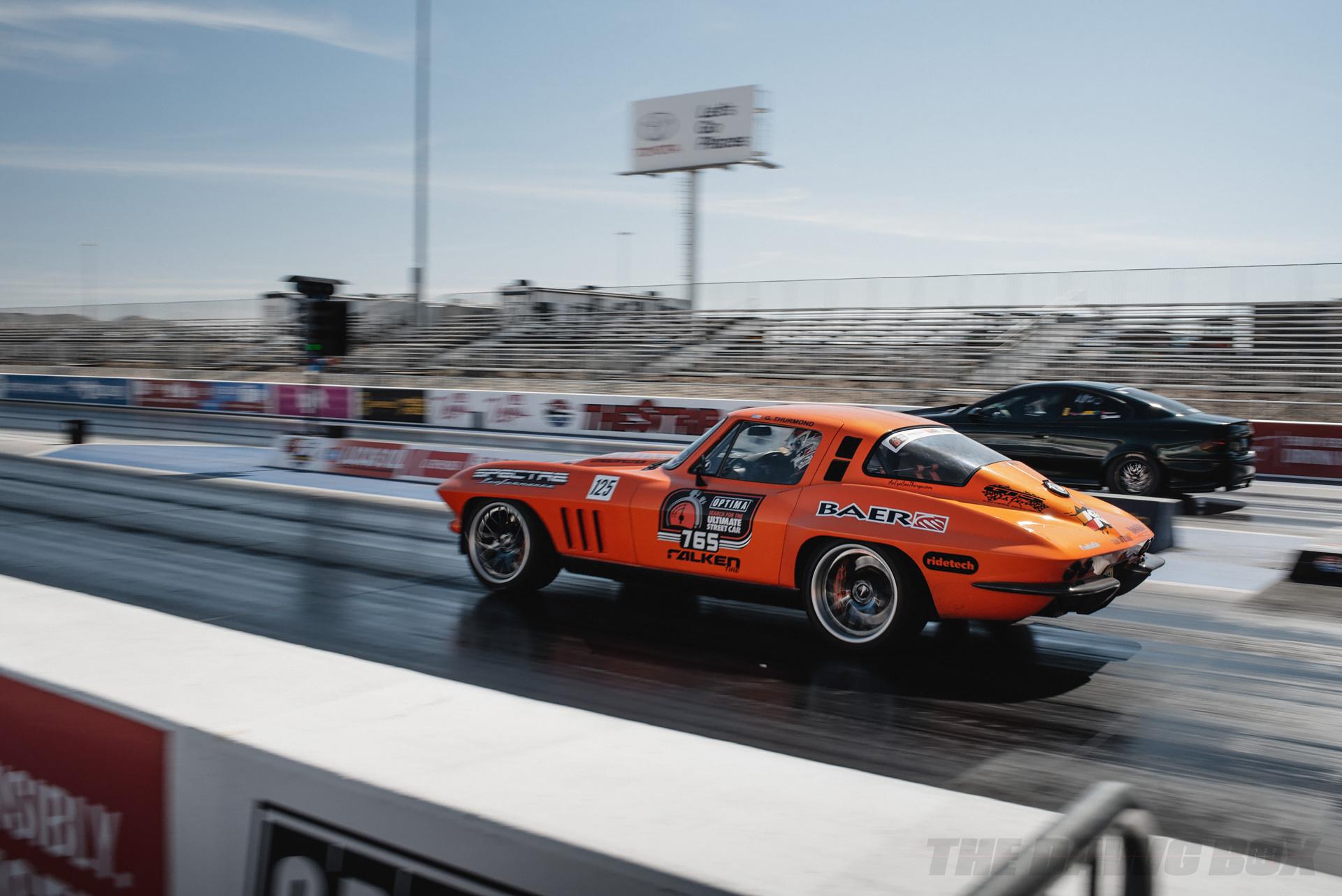 orange Chevy Camaro drag racing against a black BMW