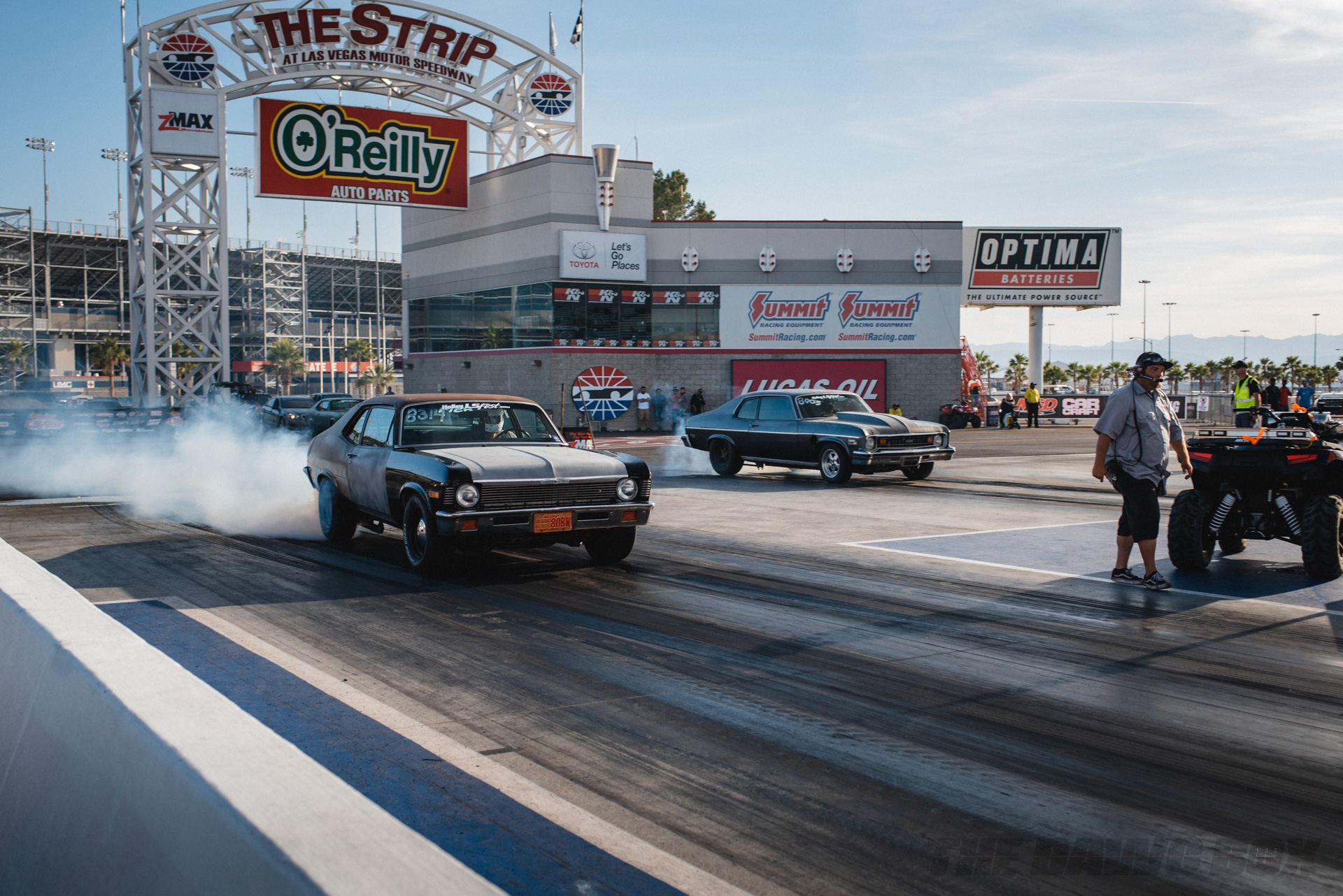 Chevy muscle cars doing burnouts and getting ready for a drag race