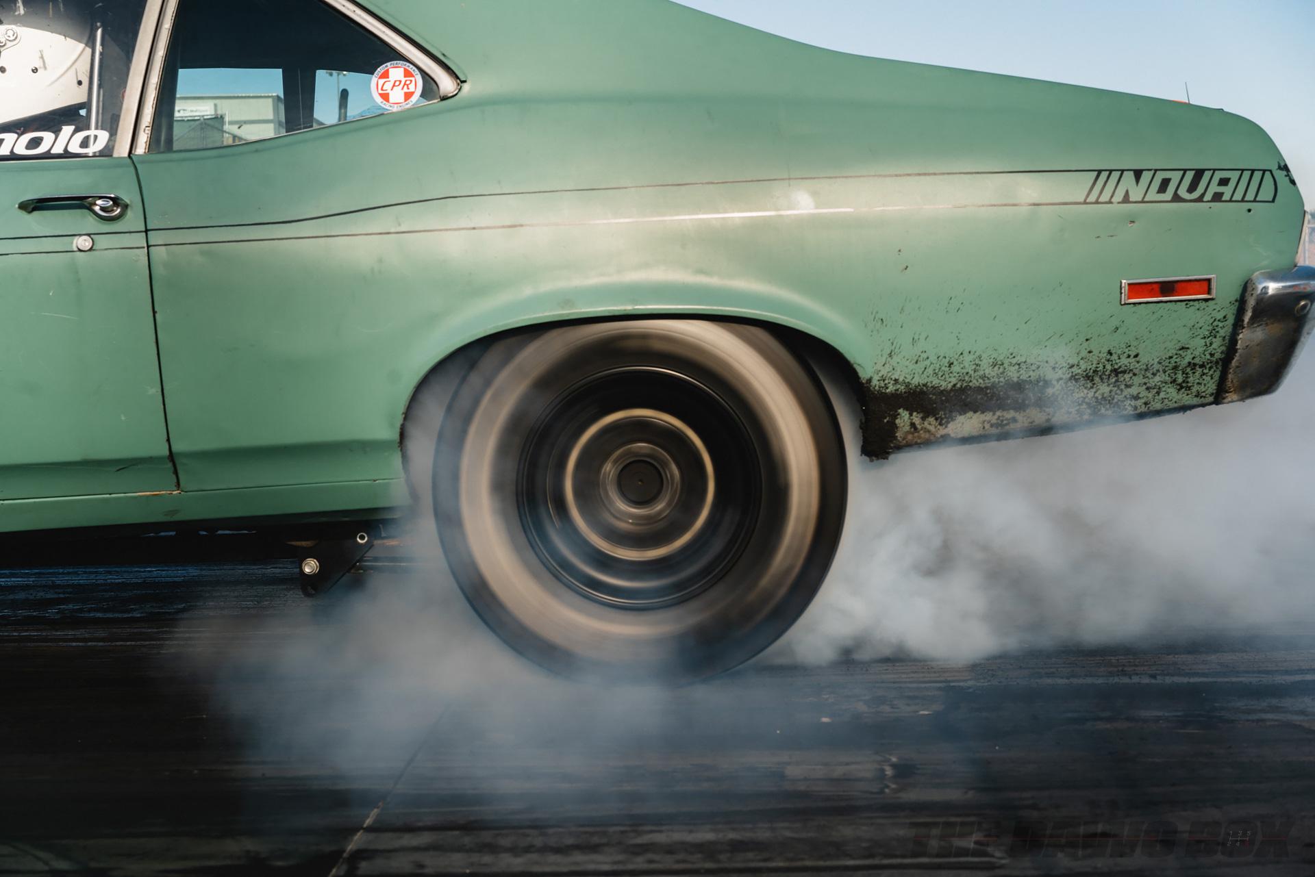 Green Chevy Nova doing a burnout