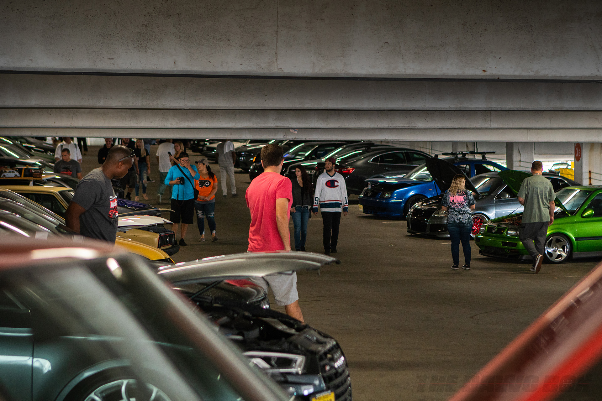 Cars lined up and displaying their engines in a parking garage