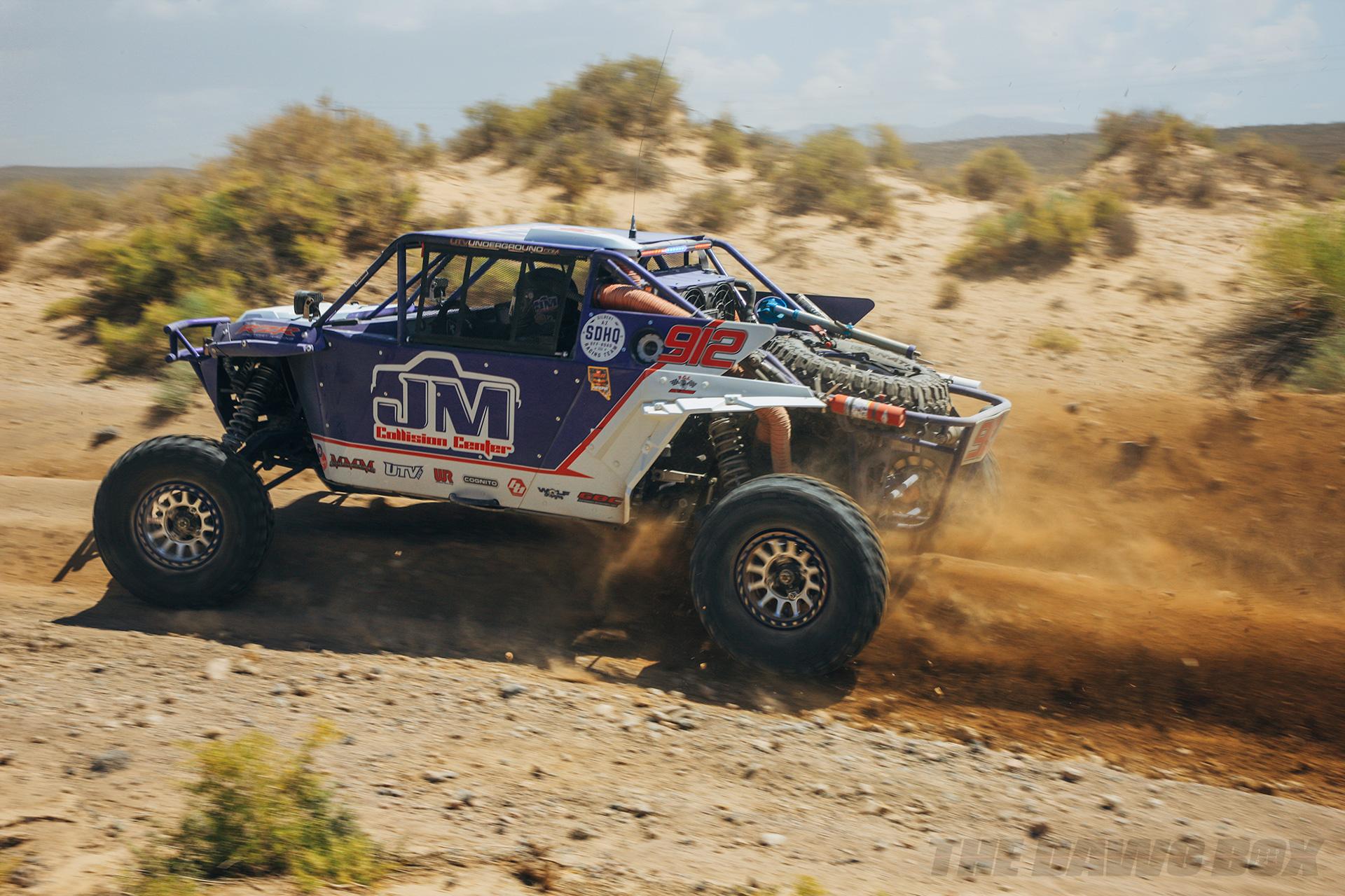 Blue JM Collision Center Rock racer speeding over a desert dirt road