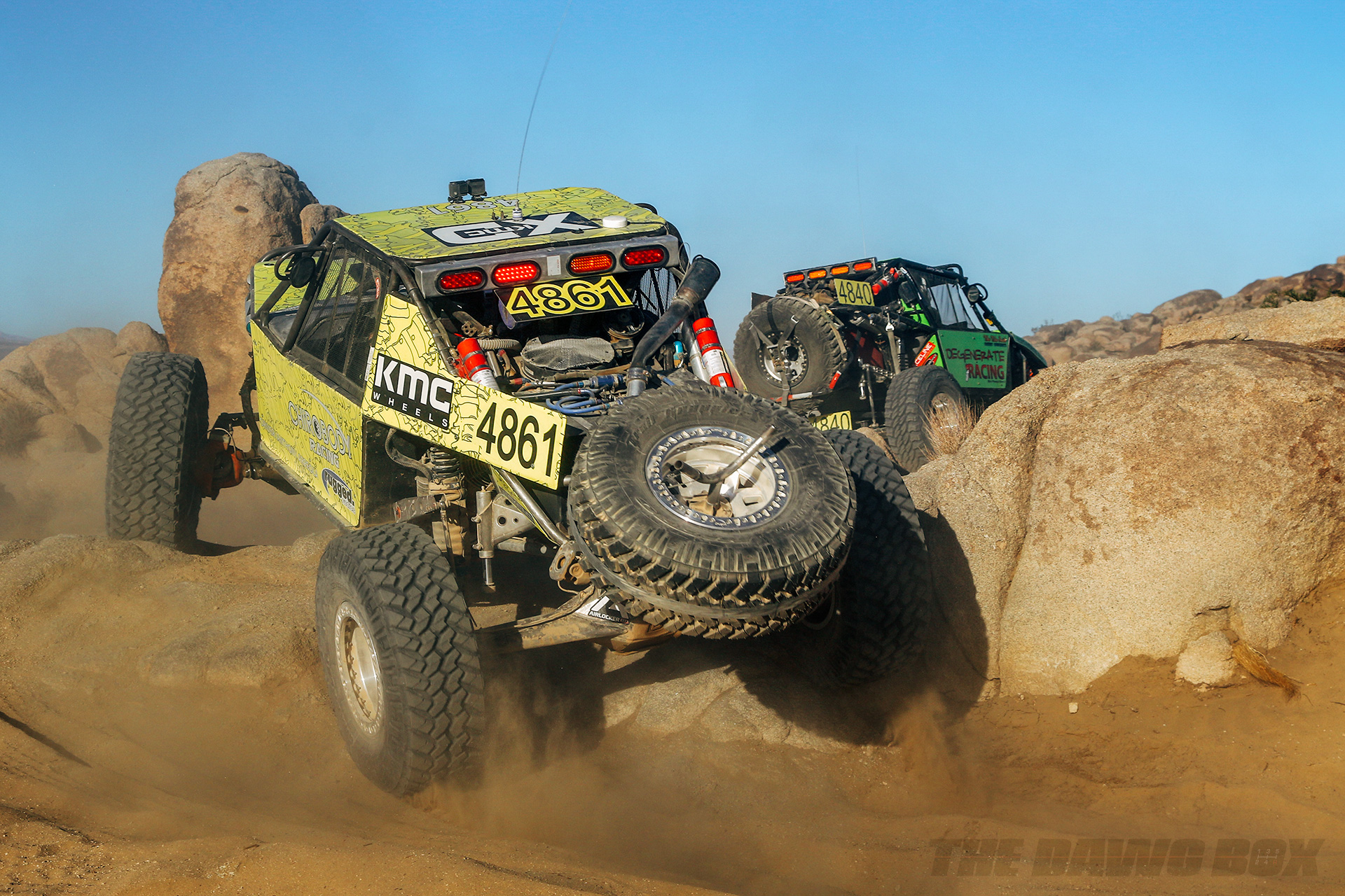 A pair of green rock racers speeding over some boulders