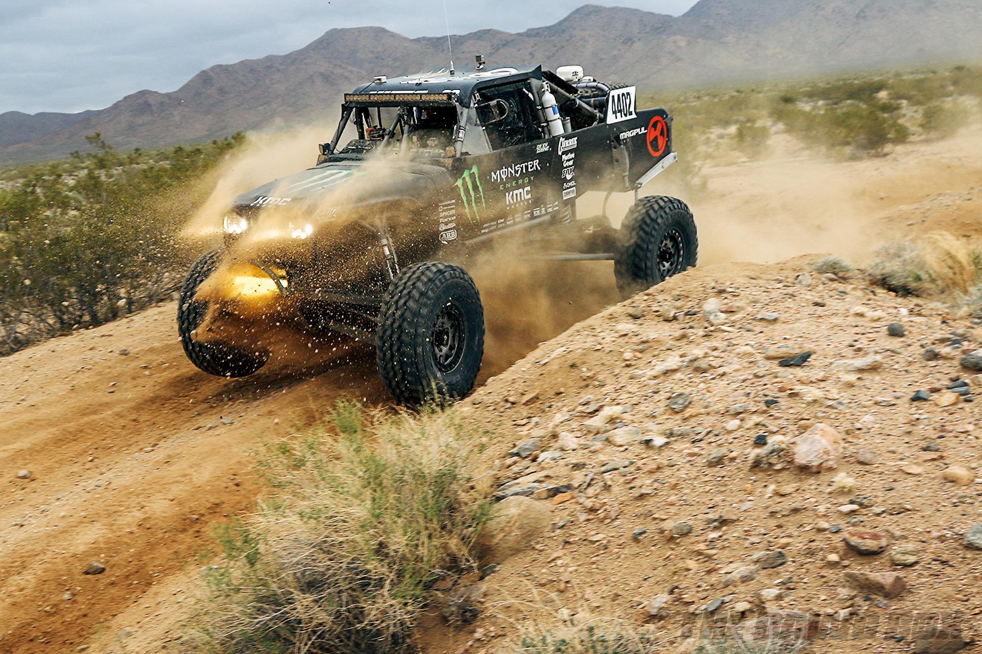 Black, Monster Energy sponsored rock racer speeding over a desert road