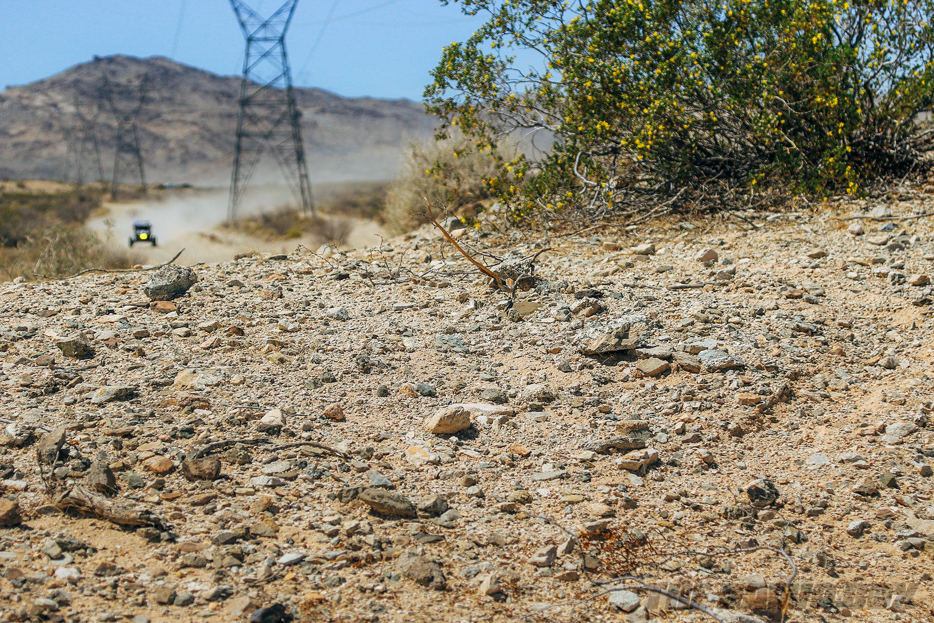 Close up of a dirt road while a rock racer speeds towards the camera in the distance