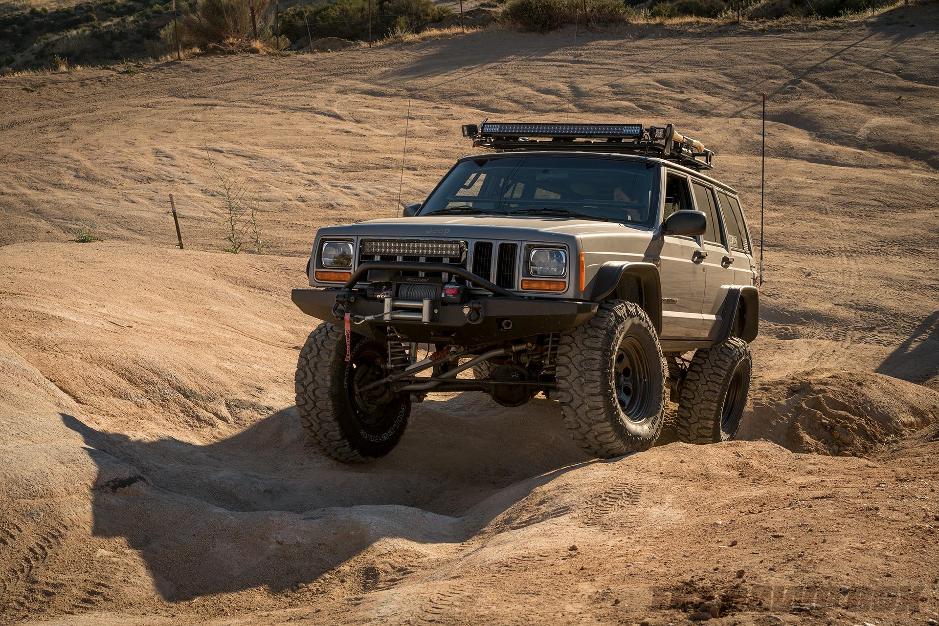 Grey Jeep Grand Cherokee crawling up some rocks