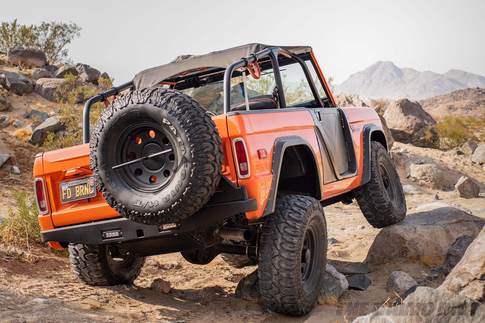 Orange Vintage 71 Ford Bronco Sport crawling off-road