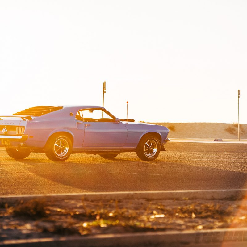 Side shot of the Blue 1969 Mustang Mach 1 in a warm sunset glow at the beach