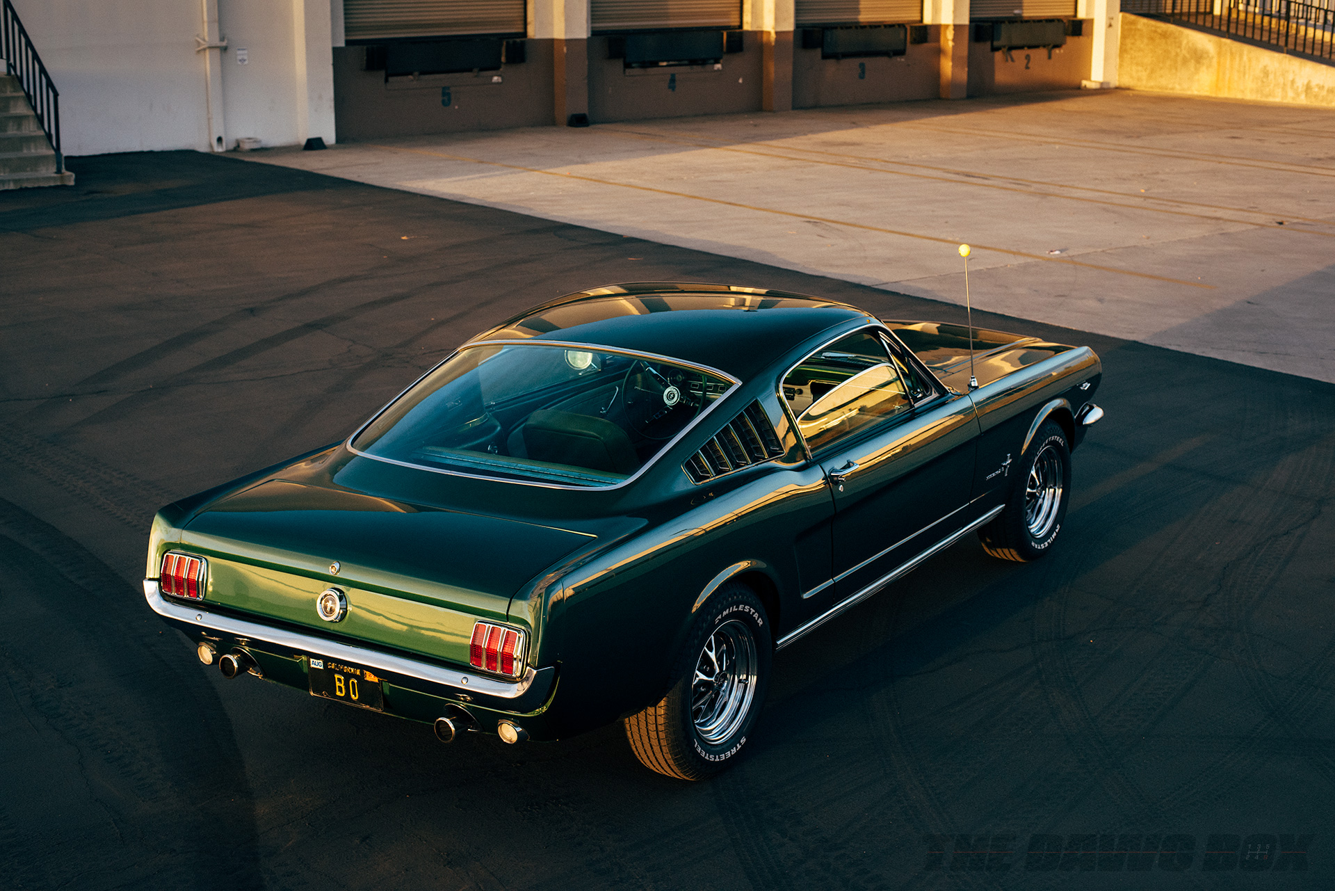 Back view of the Green 1965 Mustang Fastback 2+2 sitting in front of a shipping dock