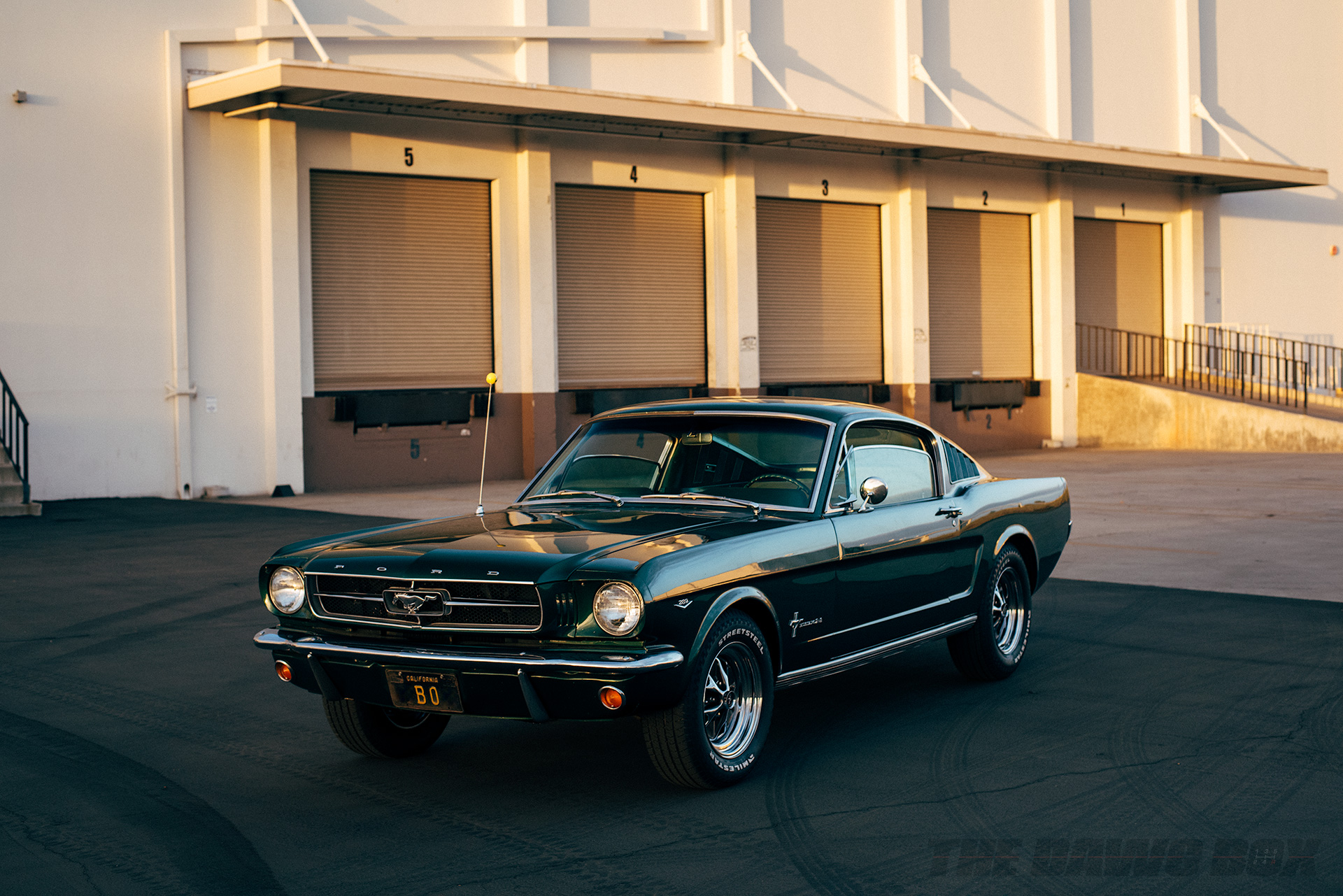 Front view of the Green 1965 Mustang Fastback 2+2 sitting in front of a shipping dock