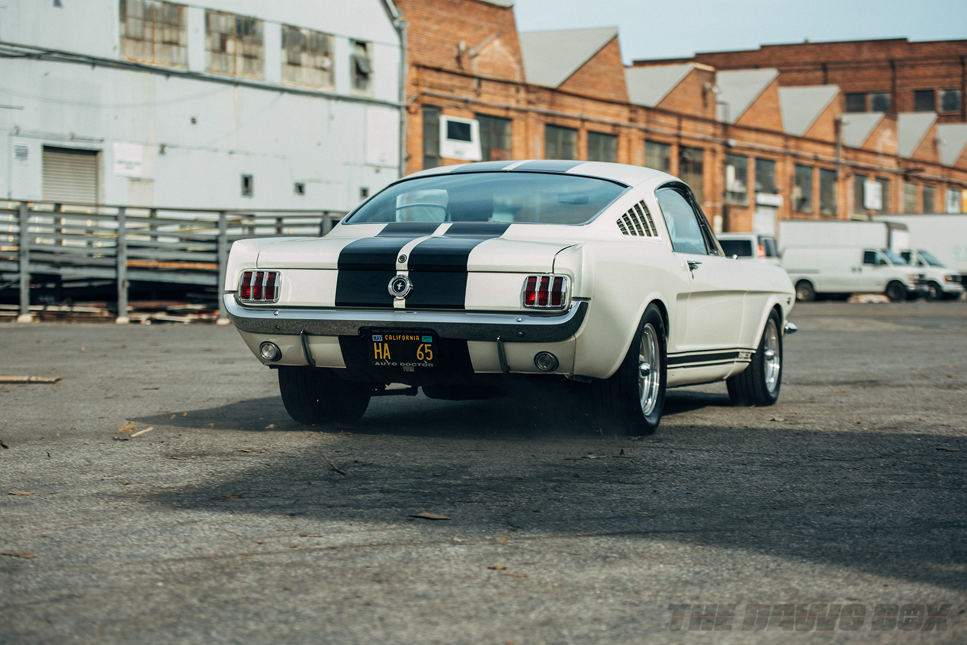 Back view of the White 1965 Mustang G.T. 350 with black stripes driving away in front of industrial buildings