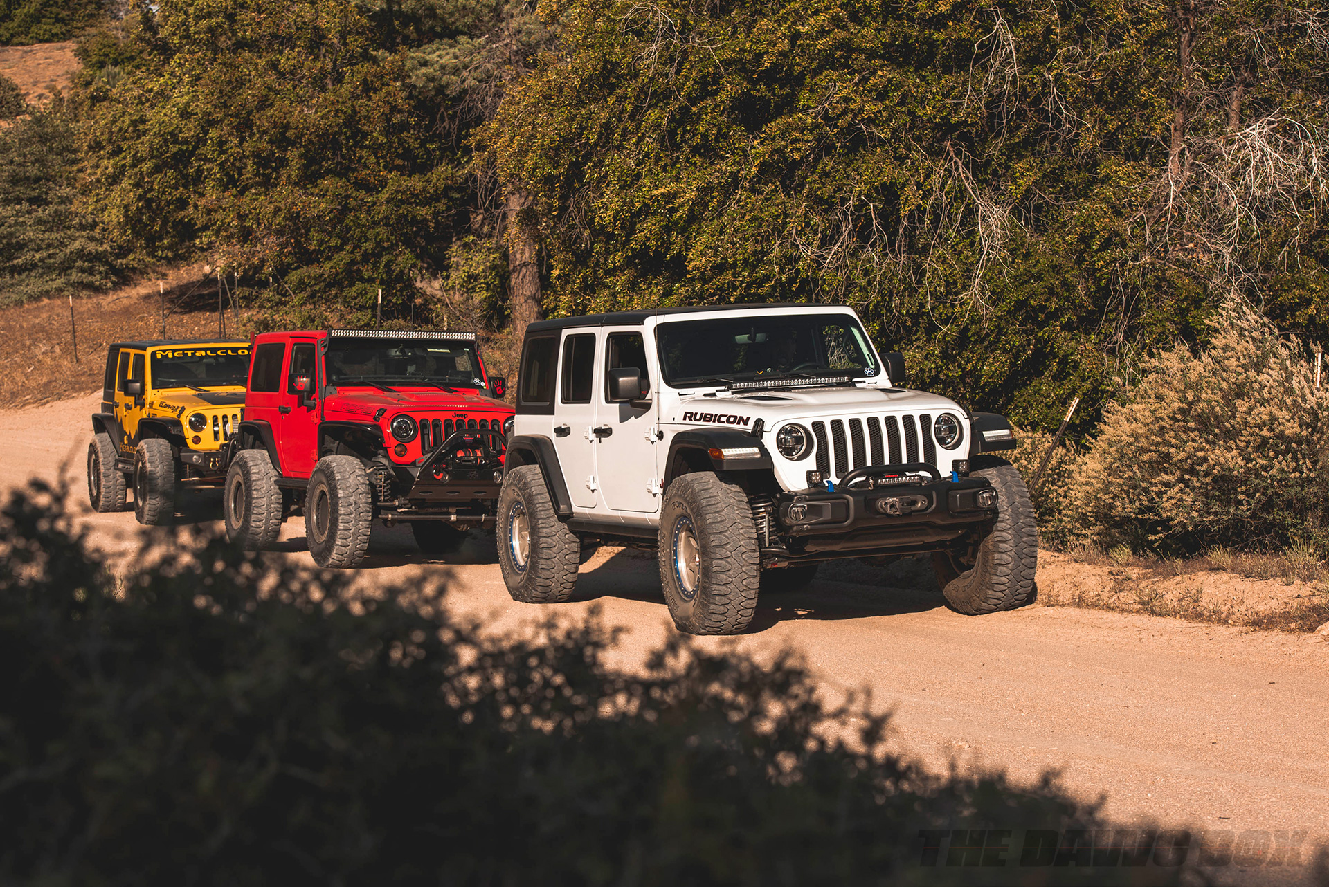 White, red and yellow Jeep JKs with 37, and 38 inch Milestar Patagonia MT tires
