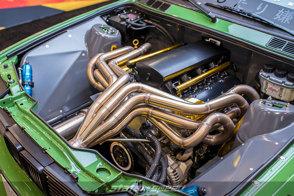 Rebellion Forge Racing green e30 with custom exhaust headers