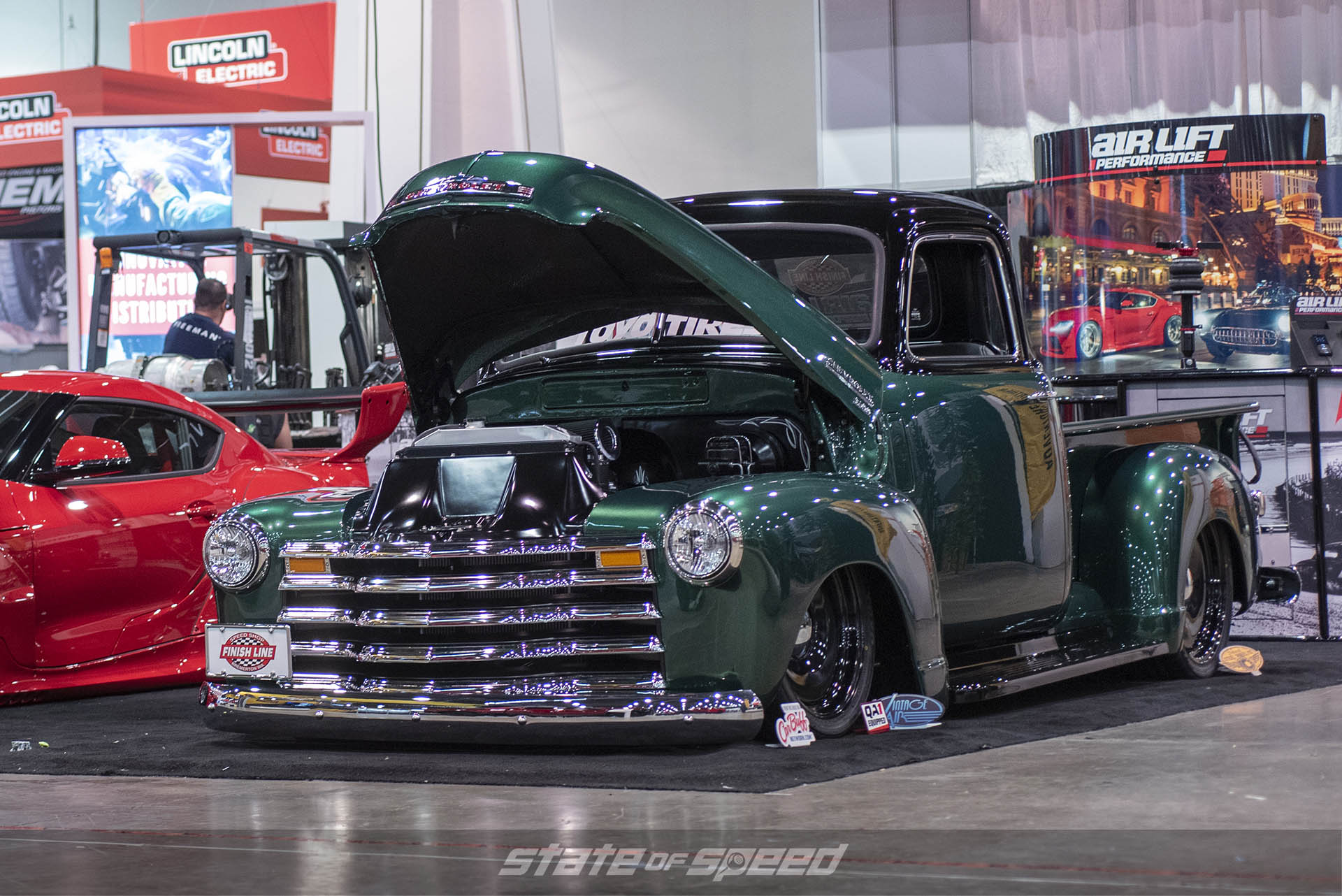Air Lift Performance booth featuring a bagged classic Chevy pickup