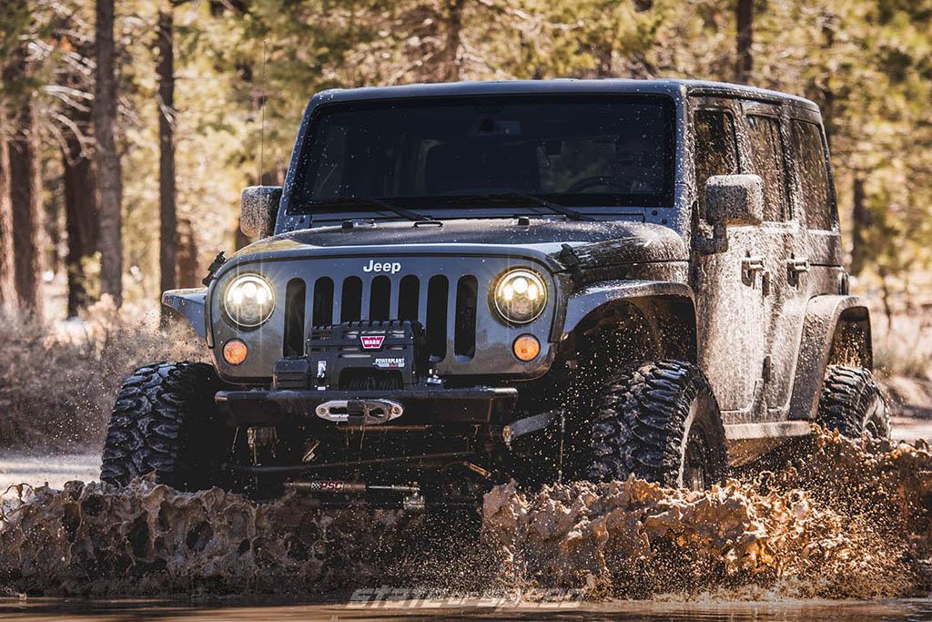 Grey Jeep JK going through mud