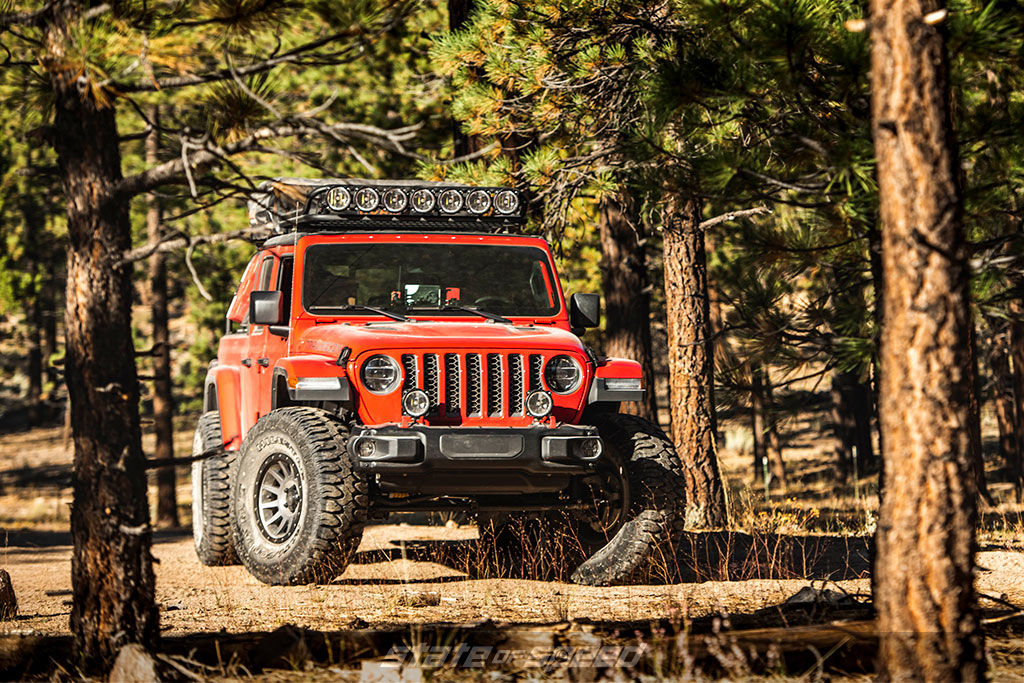 Red Jeep JT Overland vehicle in the forest with Patagonia MT