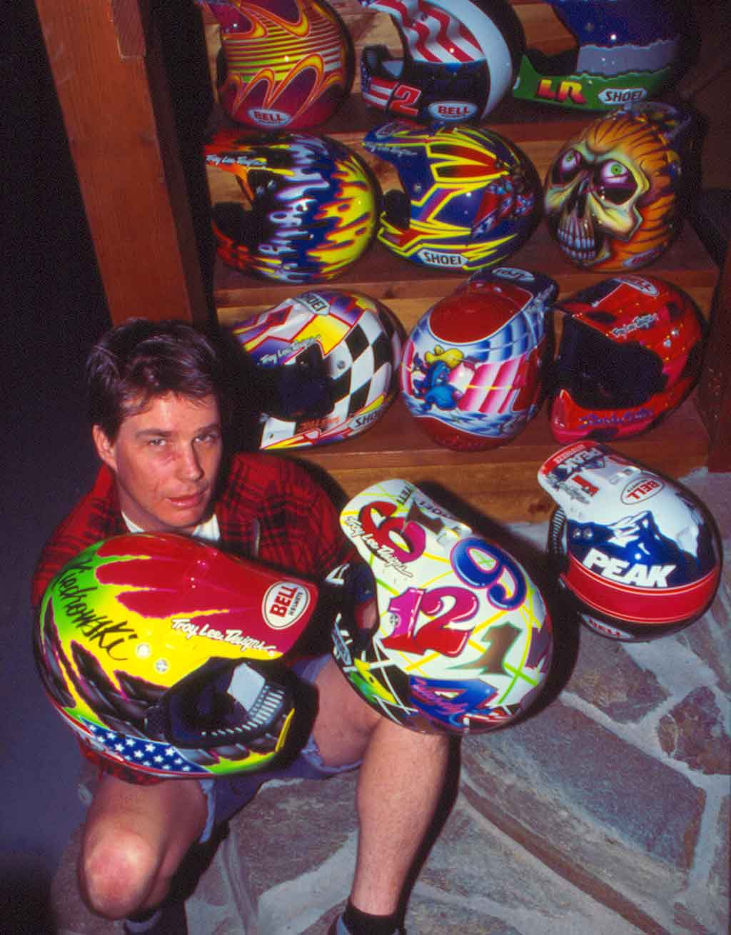 Troy with his collection of custom painted helmets