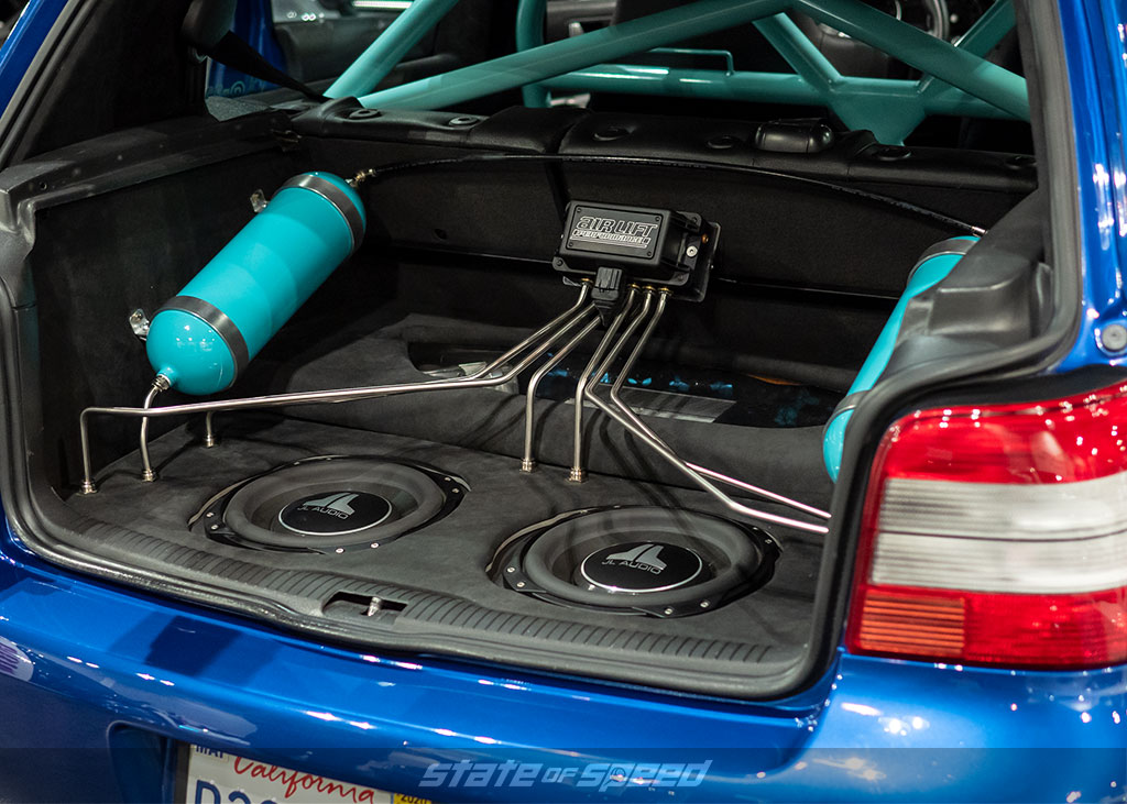 Trunk setup of bagged blue VW R32 with subs and Air Lift suspension at Slammedenuff Socal 2020