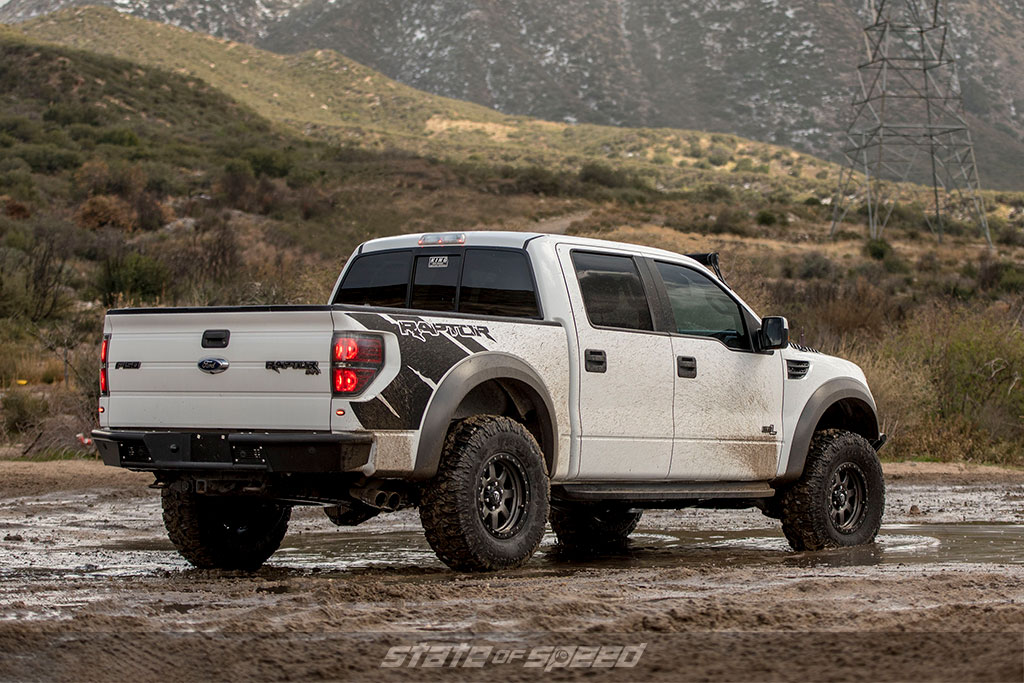 White Ford Raptor trekking through the mud. One of the best off road vehicles