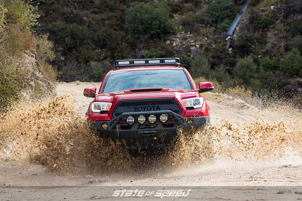 Red toyota tacoma with a light bar offroading