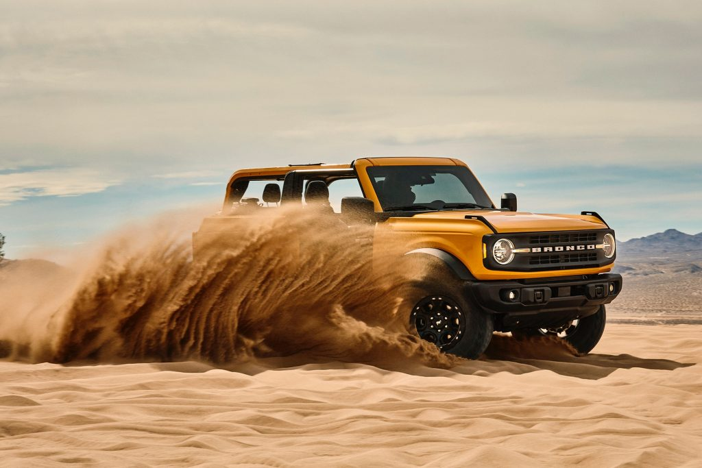 Orange Yellow 2021 Ford Bronco in running in the desert sand