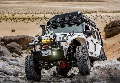 White Jeep JK Overlander crawling over rocks