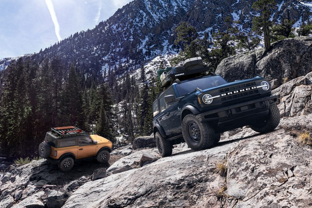 pair of Ford Broncos climbing rocks in the mountiains