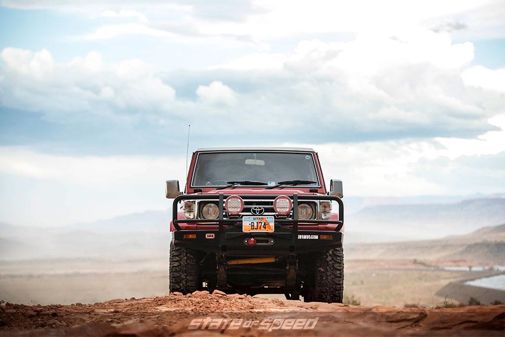 Red Toyota Land Cruiser crawling rocks