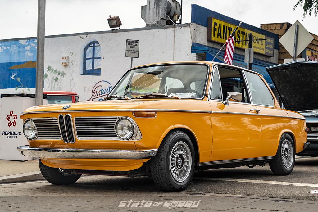 Orange 1960's BMW 2002 in front of a store at a car meet during an overcast day