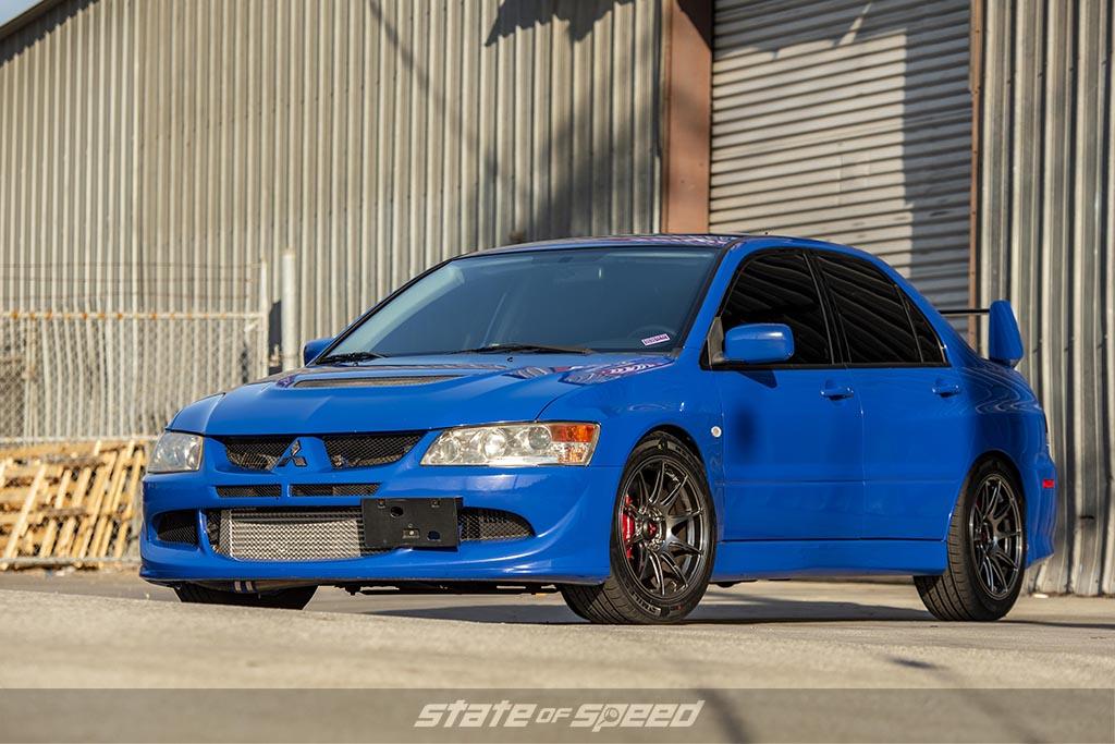 Blue Mitsubishi Evo near a warehouse