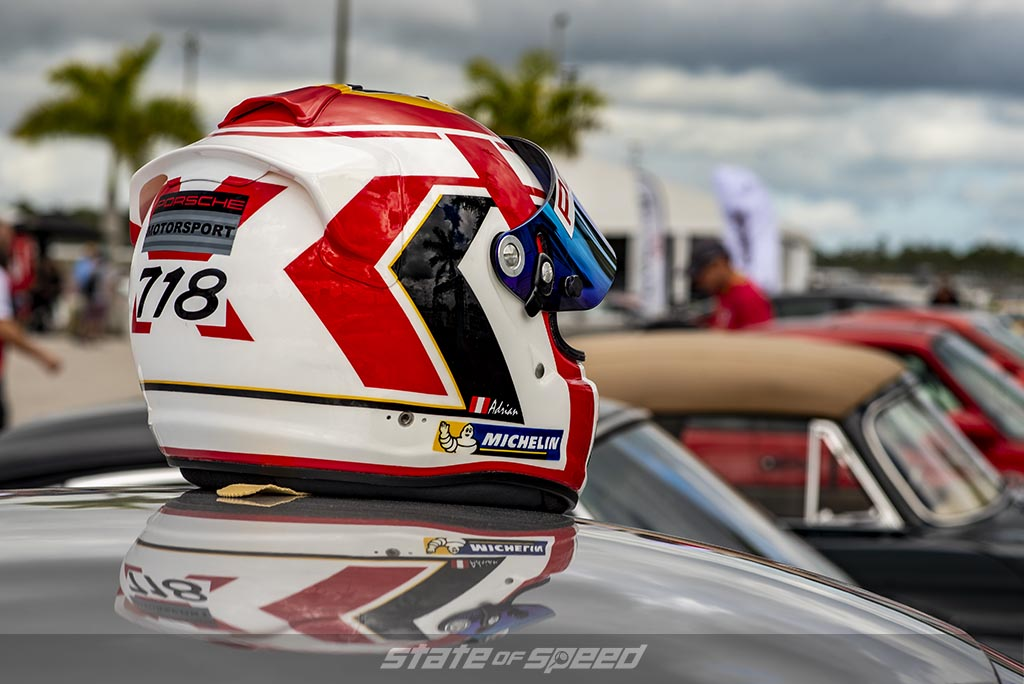 red, black , and white helmet sitting on top of a car at a track day event