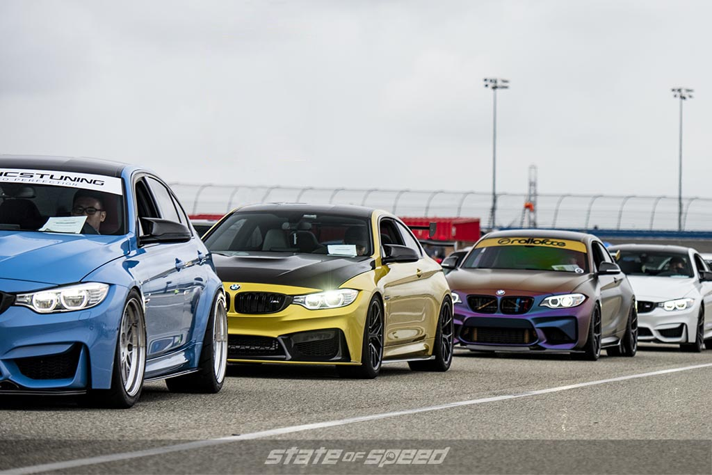 blue, yellow, purple, and white M series BMWs getting ready to race around a track