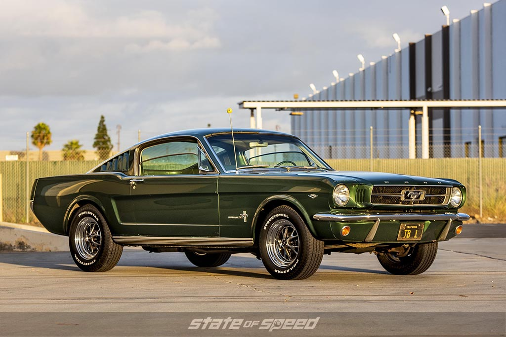 Green 1965 Ford mustang fastback 2+2 on milestar streetsteel tires during a sunset