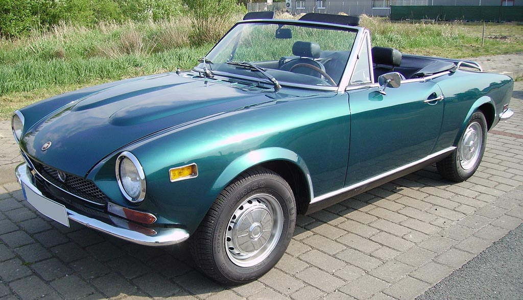 Teal 1968 Fiat 124 Spider on a brick road