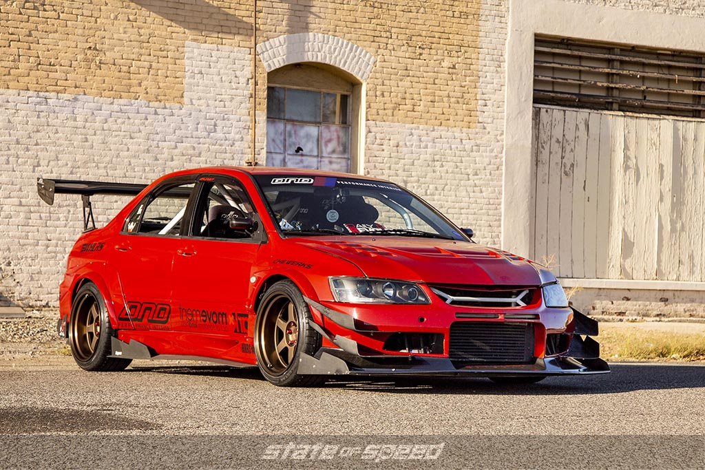 modified Red Mitsubishi Evo on Milestar MS932 XP+ Tires with a rustic background during a sunset