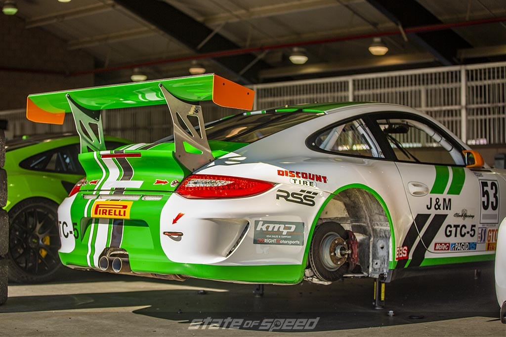 Green and White porsche 911 on jack stands without wheels in a garage at a track