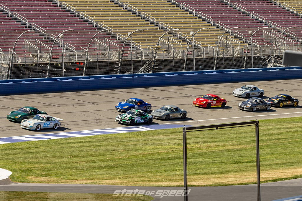various porsches race around a track