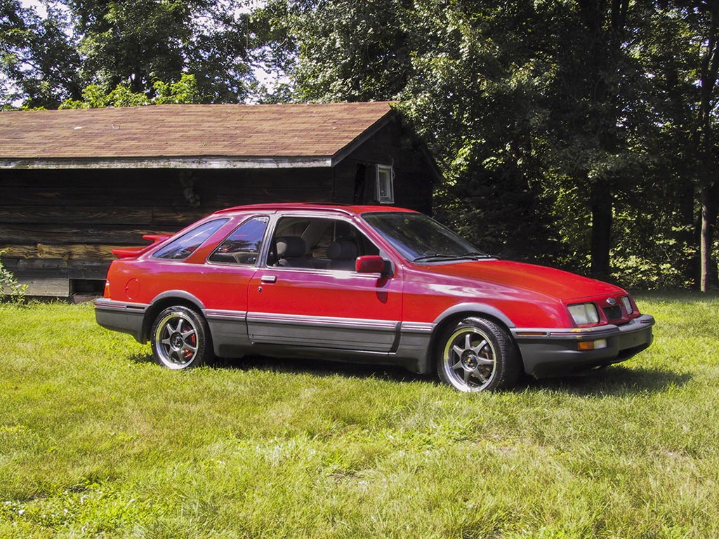 Red ford Merkur XR4Ti with custom wheels parked next to a cabin